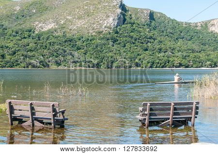 NATURES VALLEY SOUTH AFRICA - MARCH 2 2016: Two benches and a lone rower in an overfull lagoon at the mouth of the Groot River at the small town of Natures Valley