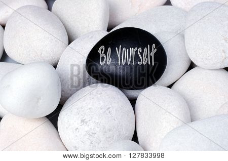 Being different stand out of a crowd conceptual zen stones with words