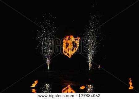 Burning heart with fireworks. Wedding show. Fire show at night.