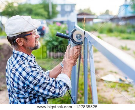 man builds a metal fence. construction worker with an angle grinder in his hands