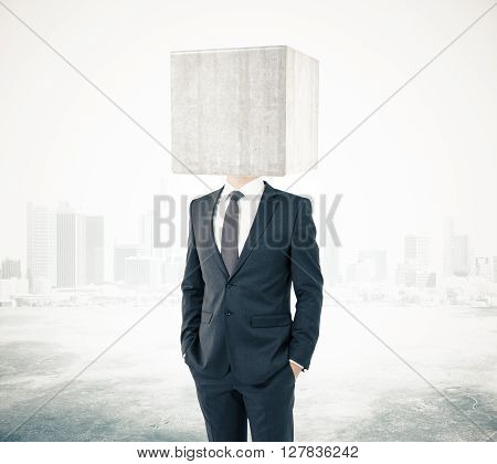 Businessman with concrete box instead of head on foggy city background