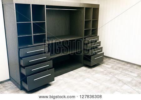 Sideview of dark wooden cupboard in concrete interior. 3D Rendering