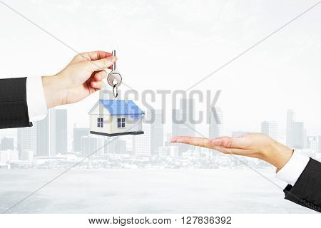 Mortgage concept with businessman handing house with key to another man on foggy city background
