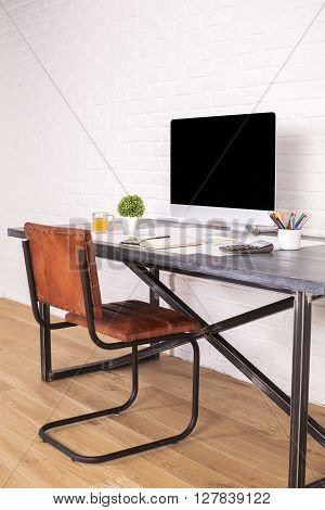 Sideview of desk with blank computer screen and brown chair next to it on wooden floor and brick background