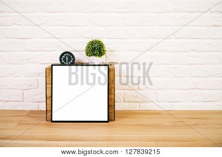 Closeup of table with blank picture frame leaning on wooden box with flowerpot and clock on top. White brick background. Mock up