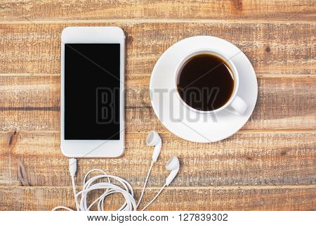 Topview of cellphone with headphones and coffee cup on antique wooden table. Mock up