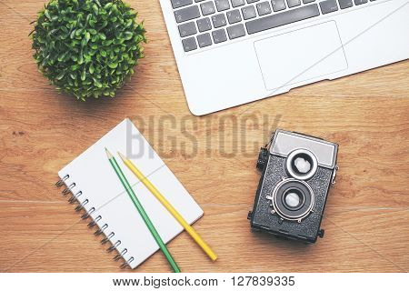 Topview of desktop with plant laptop keyboard notepad with pencils and retro camera