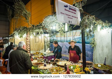 STRASBOURG FRANCE - APR 24 2016: People buying traditional olives and tapenades at the traditional french cusine covered market