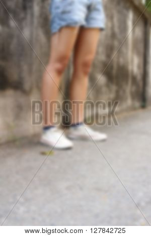 Blurred of woman stands near the brick wall.