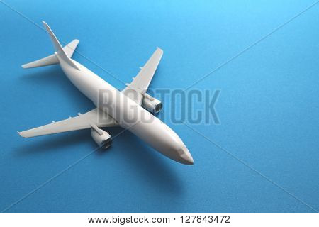Miniature of toy airplane on blue background.