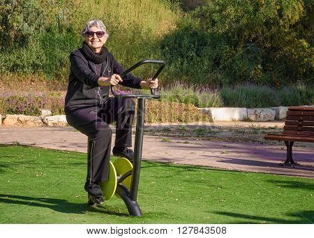 76-year-old woman in sunglasses tries out spinning cycle trainer in her local park. Grey-haired woman in black sport suit is working out at outdoor gym. She improves co-ordination while strengthen the back arms and legs. Promote health and well-being life