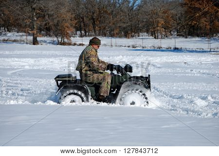Man in camo riding quad wheeler through the snow.