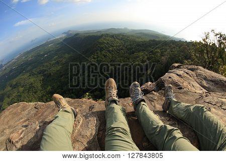 two hikers legs enjoy the view on mountain peak