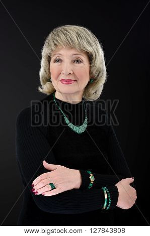 Portrait of stunning 76-year-old woman wears malachite stick bar beads bracelets watch and rings. She crosses her arms on black turtleneck shirt. The woman has on ash blonde wig. Upper body vertical shot on black background