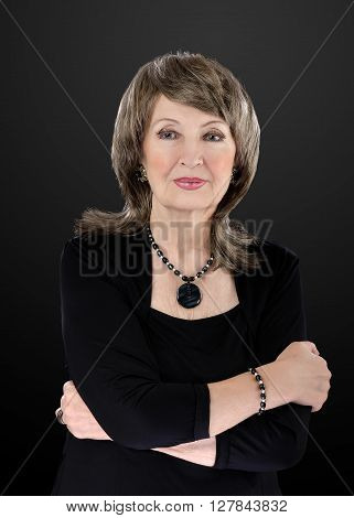 Portrait of gorgeous 76-year-old woman wears blue tiger eye beads necklace with donut and bracelet. She crosses her arms. The woman has on brown and ash blonde wig. Upper body vertical shot on black background.