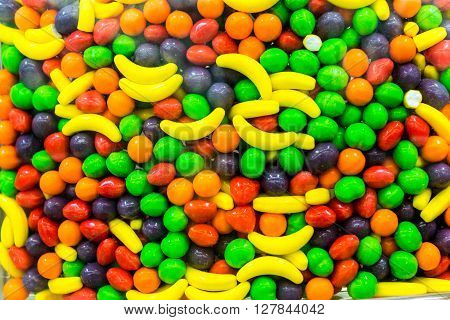 A bulk food bin filled with colorful candy drops in all flavors