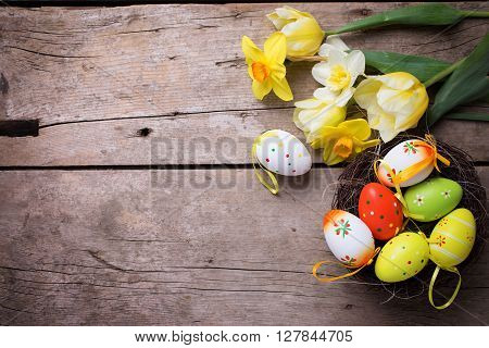 Easter background. Fresh yellow tulips and daffodils flowers decorative eggs in nest on vintage wooden background. Selective focus. Place for text.