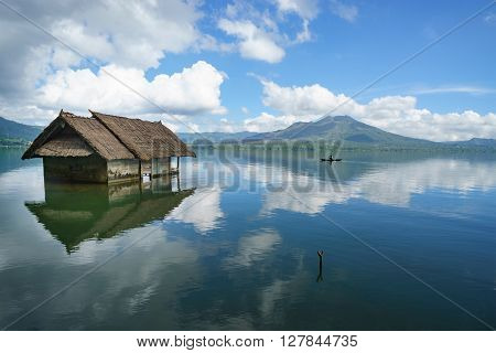 Abandoned submerge house with unrecognizable man fishing in the middle of the Lake Batur overlooking Mount Batur suring cloudy bluesky in Bali Indonesia.