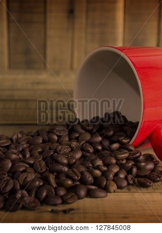 coffee beans and red cup on the wooden table Concept filter sepia. ** Note: Shallow depth of field