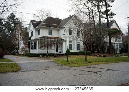 HARBOR SPRINGS, MICHIGAN / UNITED STATES - DECEMBER 23, 2015: A white home with a wraparound front porch on Second Street in Harbor Springs.