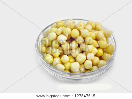 Germinated chickpeas in a transparent glass jar on a white background