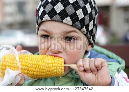 Child eating corn in the park in spring