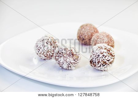 Homemade raw dates truffles with nuts psyllium and coconut flakes on a white plate and white background