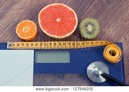 Electronic bathroom scale for weight of human body tape measure and stethoscope with fruits copy space for text on sheet of paper healthcare healthy lifestyles and slimming concept