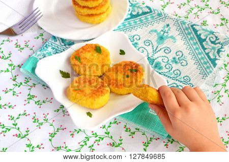 Fried rice patties on the plate. Easy vegetarian recipe. Child takes one cutlet