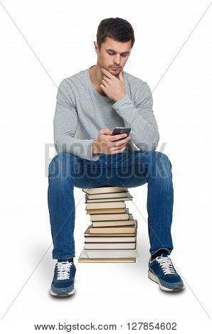 Young man looking for information in the phone and not in the books