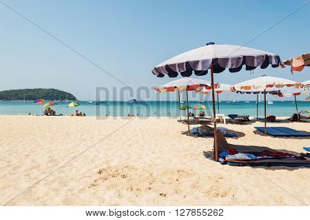 Phuket Thailand - March 01 2016: Blue sea and parasol with some people relax on the white sand beach
