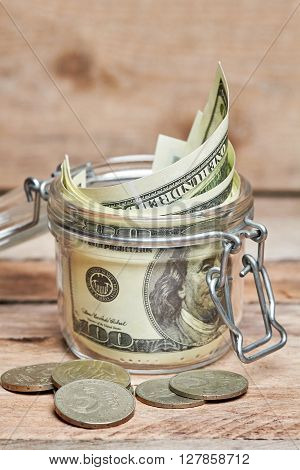 Glass jar with dollar banknotes and five coins