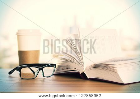 Spectacles cup of coffee and open book on wooden desktop