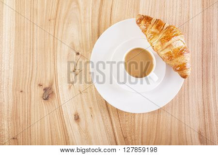 Topview of wooden desktop with cup of coffee and croissant on plate. Mock up