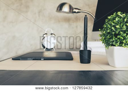 Sideview of desktop with graphic tablet plant alarm clock lamp and computer. Concrete wall background