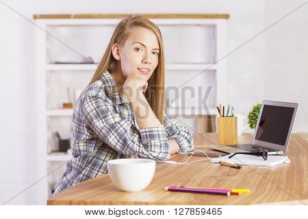 Pretty caucasian female sitting at office desk with hand at chin. Sideview