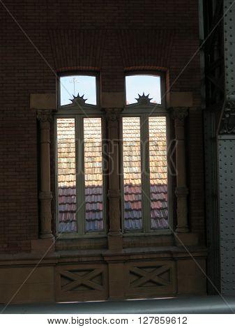 Looking through ornate window unto sunlit roof at Atocha station Madrid