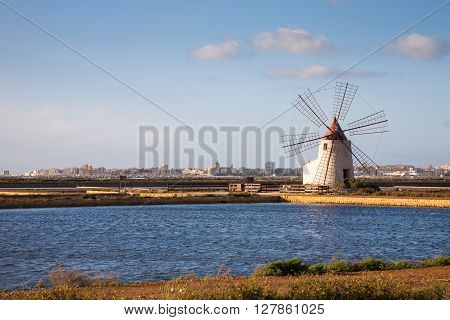 A windmill in a salt pan withTrapani in the background in the western part of Sicily in Italy