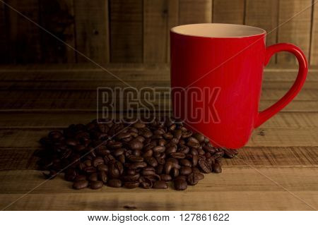 coffee beans and red cup on the wooden table Concept filter sepia.