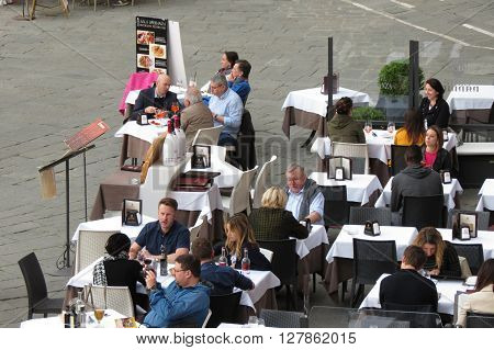 SIENA ITALY - CIRCA APRIL 2016: unidentified people having dinner at outdoor terrazzo restaurants in the city centre