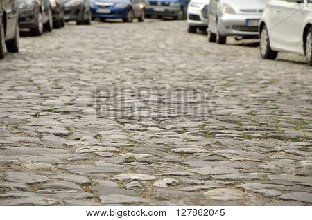 Street in old part of town paved with stone and with parked cars