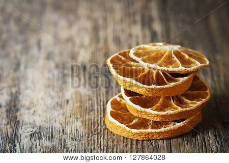 Slices of dried oranges on a vintage wooden background close-up. Dried fruits. Copy space background. Selective focus