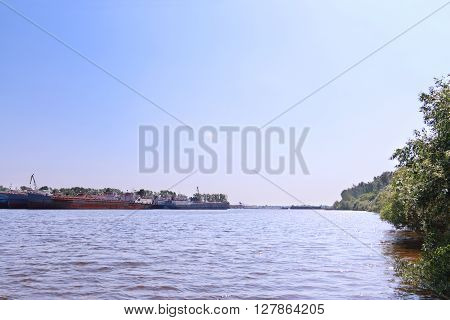 River with cargo ships and shore overgrown bushes on summer day