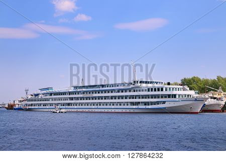 Motor boat next to large passenger white ship on river in summer sunny day