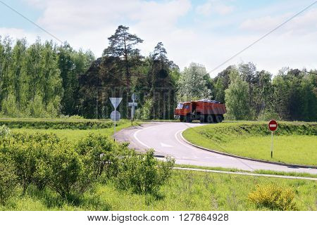 Orange Dump Truck moves on road on hill in green grass at sunny day