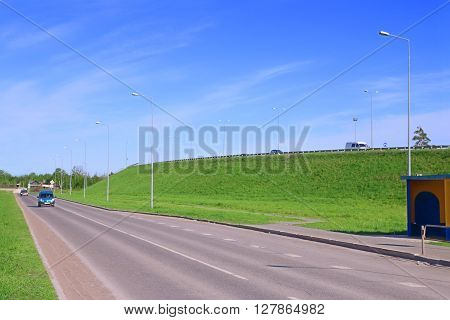 Cars move on asphalt road near hill in green grass at sunny day