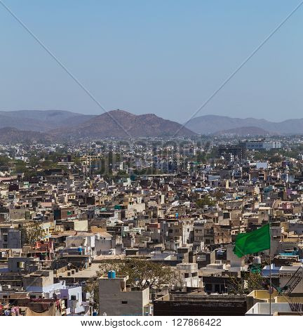 A view over rooftops in central Udaipur during the day. The Machla Hills can be seen in the distant.