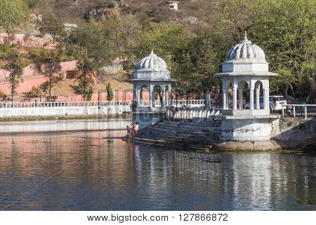 UDAIPUR INDIA - 20TH MARCH 2016: A view of the Doodh Talai Lake in Udaipur during the day. Part of the architecture at the waterfront and people can be seen.
