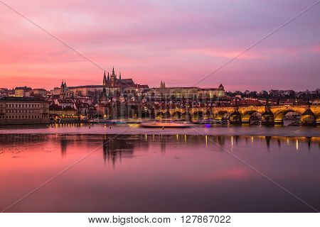 Charles Bridge in Prague towards the Lesser Quarter and Prague Castle at sunset with a colorful vibrant pink sky.