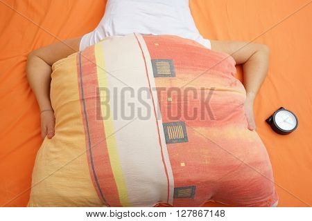 woman with insomnia female holding pillow over head